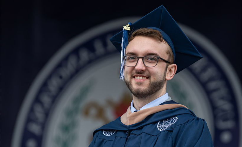 Graduating student smiling with cap and gown