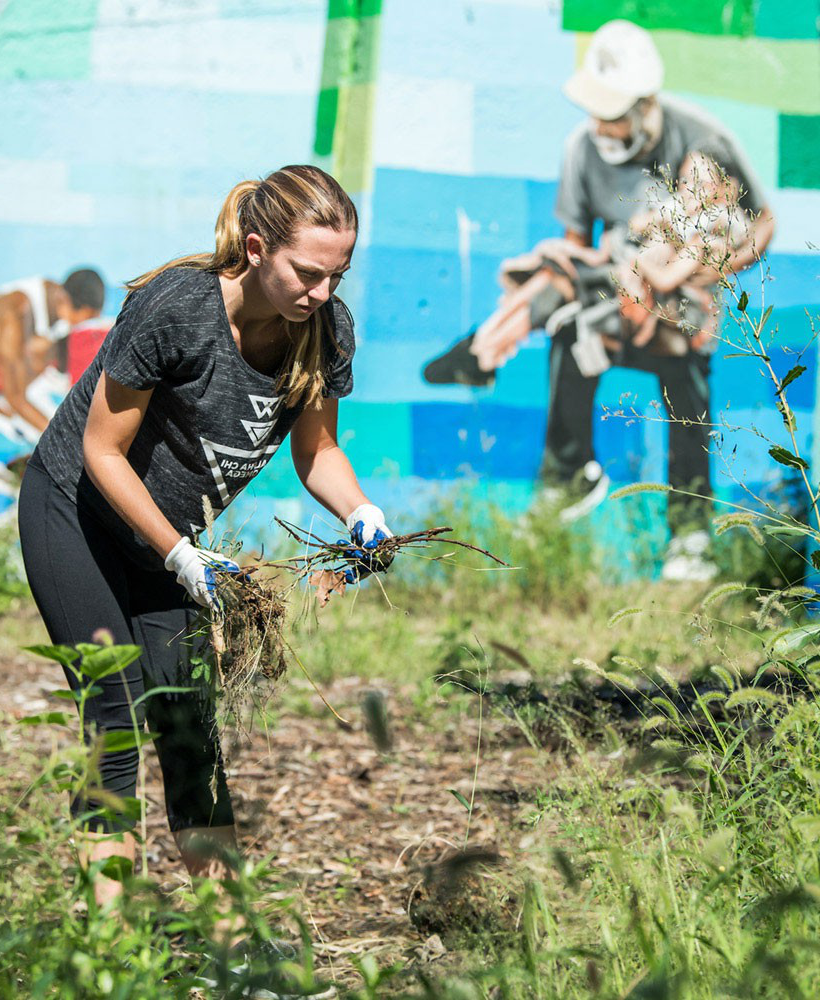 Student cleaning up a garden as part of a service project