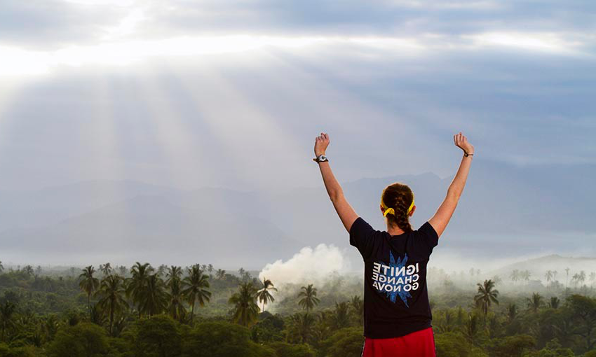 Female student in Villanova shirt raises arms above head as she looks over landscape of Peru.