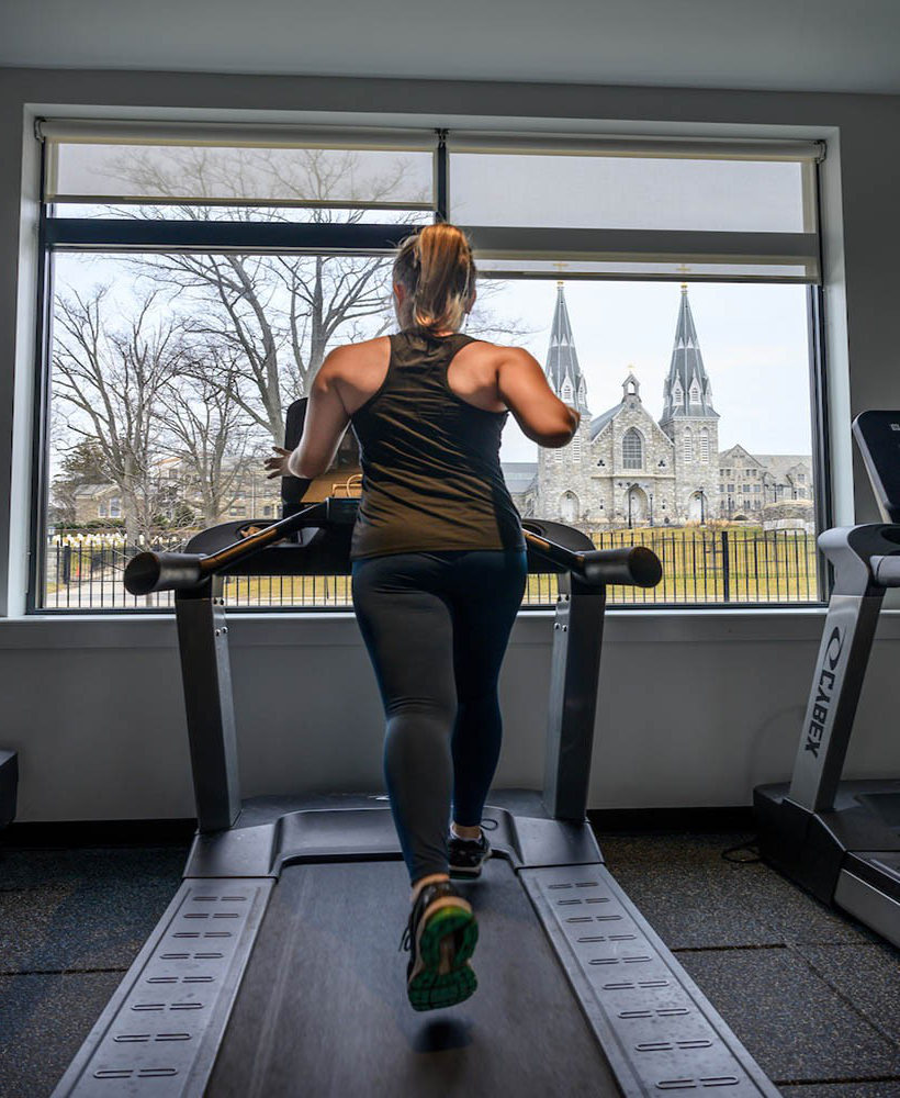 Female student on treadmill in campus workout room.